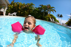 Little girl learning to swim in a swimming pool Stock Images