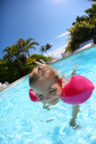 Little girl learning to swim in swimming pool Stock Photos