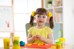 Little girl is learning to use colorful plasticine in well lit room near window. Child girl is learning to use colorful plasticine in well lit room near window Royalty Free Stock Image