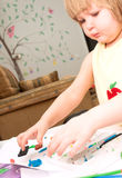Little girl is learning to use colorful play dough. Child moulds from plasticine on table Stock Photos