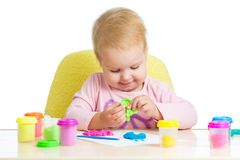 Little girl learning to use colorful play dough isolated on white background. Child little girl learning to use colorful play dough isolated on white background Royalty Free Stock Photo