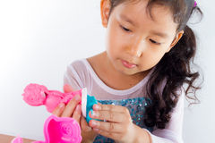 Little girl is learning to use colorful play dough. On white background Stock Photos