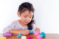 Little girl is learning to use colorful play dough. On white background Royalty Free Stock Photography