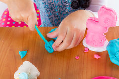 Little girl is learning to use colorful play dough Stock Images
