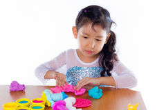 Little girl is learning to use colorful play dough. On white background Stock Images