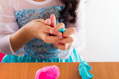 Little girl is learning to use colorful play dough. On white background Royalty Free Stock Photo
