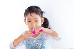 Little girl is learning to use colorful play dough. On white background Stock Photo