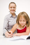 Little girl learning to write. A young teacher and student learning to write together, the teacher helping her student - against white wall Royalty Free Stock Image