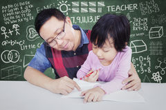 Little girl learns in the class with male teacher. Cute female elementary school student try to write on the book with male teacher in the classroom Royalty Free Stock Photo