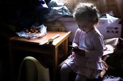 A little girl learns about the Internet through a mobile phone. Cheerful young little girl children using laptop computer with headphones studying through royalty free stock photography