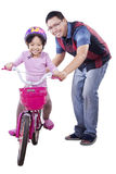 Little girl learns riding a bike with dad Royalty Free Stock Photo