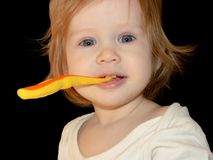 A little girl learns to brush her first milk teeth. Short-eyed Baby Girl holds her toothbrush with her teeth, looks straight and smiles at her prank stock photography