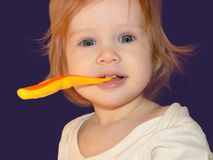 Short-eyed Baby Girl holds her toothbrush with her teeth, looks straight and smiles at her prank royalty free stock images