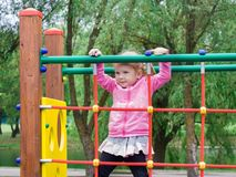 A little girl learns to climb ladders and crossbars. On the playground of the local park stock images
