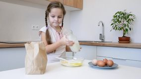 Little girl learns to cook in the kitchen and make bakery stock video