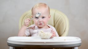 Little girl learns to eat with a spoon on her own and trains on porridge. Front view stock video footage