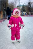 The little girl on the skates. The little girl learns to skate on a skating rink Royalty Free Stock Photography