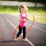Little girl learns to spin the Hoop stock image