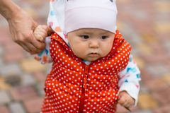 Little girl learns to walk, taking its first steps. Female hands mother support the child. Autumn Royalty Free Stock Images