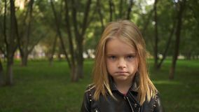 Little girl in a leather jacket fed up in a park. Serioius little blonde girl wearing a leather jacket is fed up. She is standing in a park on a summer day stock video footage