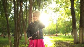 Little girl in a leather jacket listening to music in park. Cute little girl wearing a leather jacket listening to the music and dancing in a park on a summer stock footage