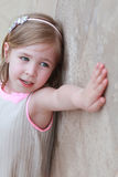 Little girl with left hand resting on a wall Royalty Free Stock Photo