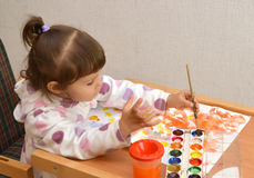 The little girl lefthander draws water color paints.  stock images