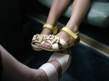 Little Girl Legs In Sandals. Little girls legs wearing sandals sitting on a bus seat, cropped shot Stock Image