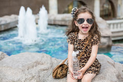 Little girl in a leopard dress sitting on a rock. With a bottle next to the fountain stock images
