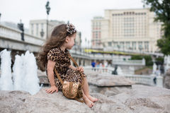 Little girl in a leopard dress sitting on a rock. Smiling little girl in a leopard dress sitting on a rock next to a fountain royalty free stock image