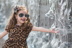 Little girl in a leopard dress touching hand fountain. Smiling little girl in a leopard dress touching hand fountain stock photo