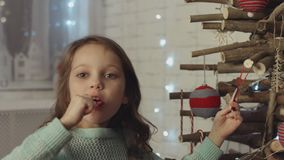 Little girl licking candy standing at the wooden Christmas tree. Little girl in the blue sweater licking candy while standing near the wooden Christmas tree stock video footage