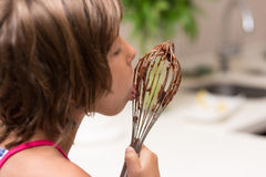 Little girl licking chocolate Royalty Free Stock Image