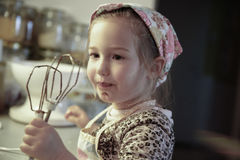 Little girl licking chocolate off the mixer beater Stock Photo