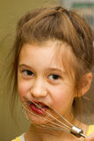 Little girl licking chocolate off the mixer beater after mixing dough for birthday cake. Permissive parenting, learning royalty free stock image