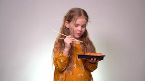 Little girl licks sushi sticks and keeps box rolls