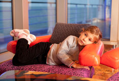 Little girl lie in chair in cabin in ship. Little girl lie in chair in cabin with large windows in large cruise ship royalty free stock image