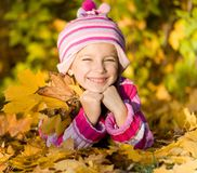 Little girl lie on the leaves Stock Photography