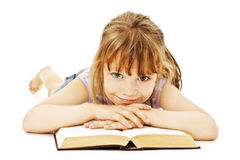 Little girl lieing on the floor and reading book Stock Photography