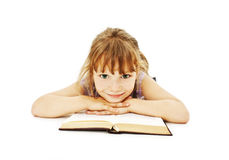 Little girl lieing on the floor and reading book Royalty Free Stock Photos