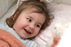 Little girl lies in bed on pillow Stock Image