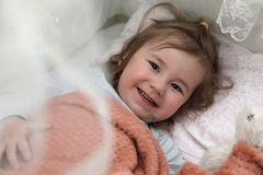 Little girl lies in bed on pillow Stock Photos