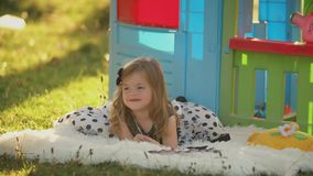 Little girl lies on a blanket. Near her toy house stock footage
