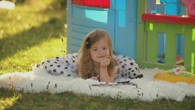 Little girl lies on a blanket. Near her toy house stock video footage