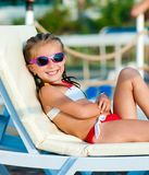Little girl lies on a chaise lounge Stock Photos