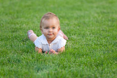 Little girl lies on the grass. Curious baby is lying on the summer meadow Royalty Free Stock Image