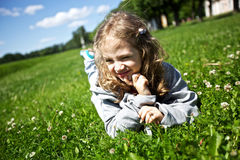Little girl lies on a green field Royalty Free Stock Photo