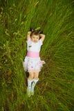 Little girl lies in green grass Stock Photo