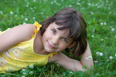 The little girl lies on a lawn. The little girl lies on a green lawn Royalty Free Stock Photo