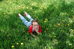 Little girl lies on a lawn. Royalty Free Stock Image